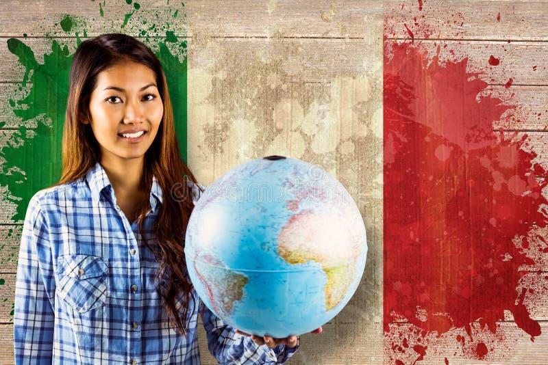Imagem composta da mulher asiática de sorriso que guarda um globo foto de stock royalty free