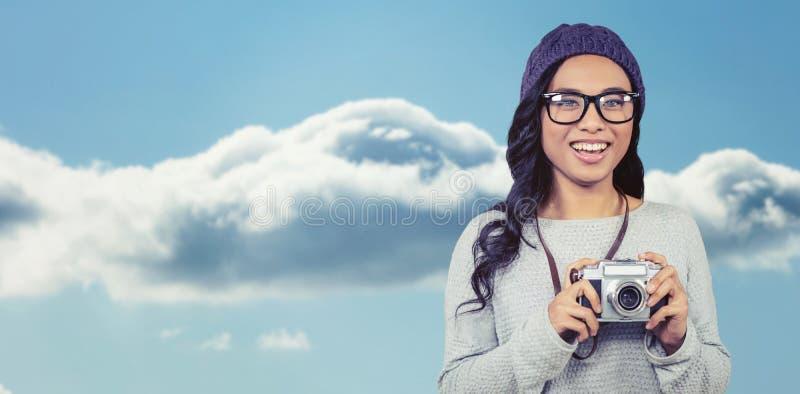 Imagem composta da mulher asiática que guarda a câmara digital imagem de stock