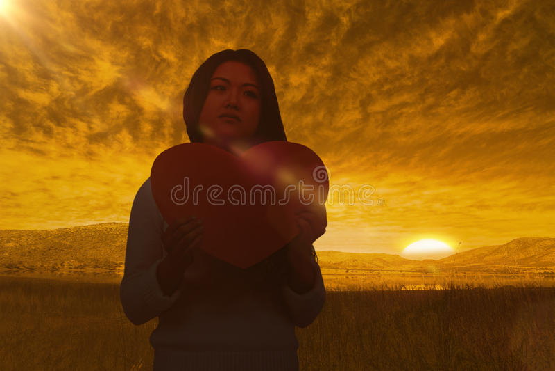 Imagem composta da mulher asiática que guarda o coração de papel imagem de stock royalty free