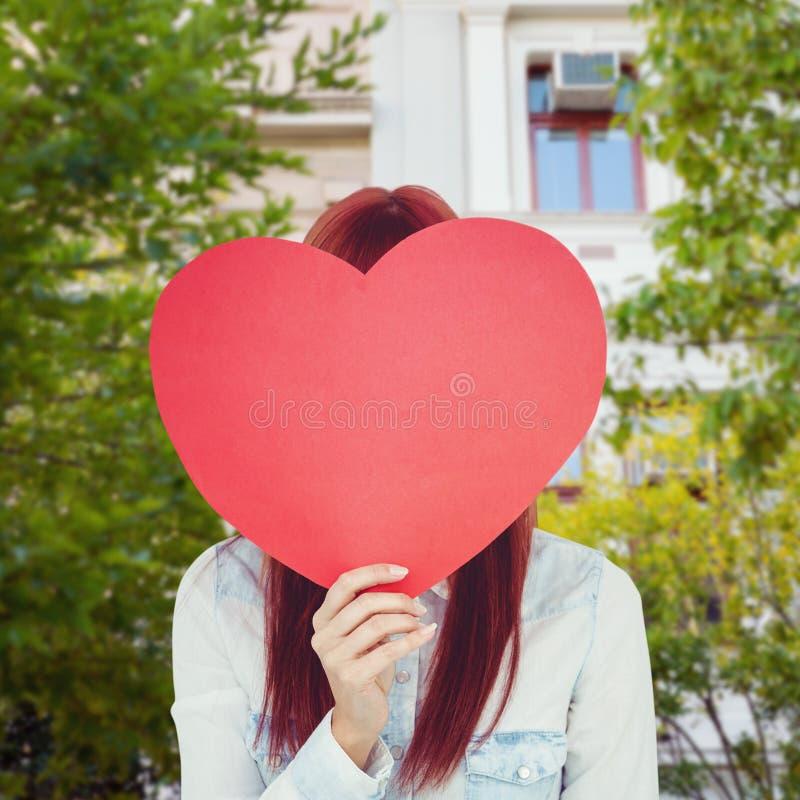 Imagem composta da mulher atrativa do moderno atrás de um coração vermelho imagens de stock royalty free
