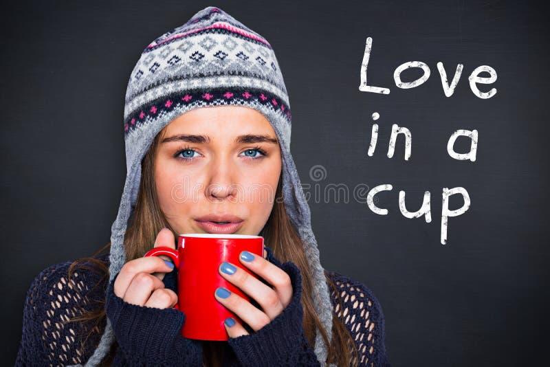 Imagem composta da mulher bonita no café bebendo da roupa morna imagens de stock royalty free