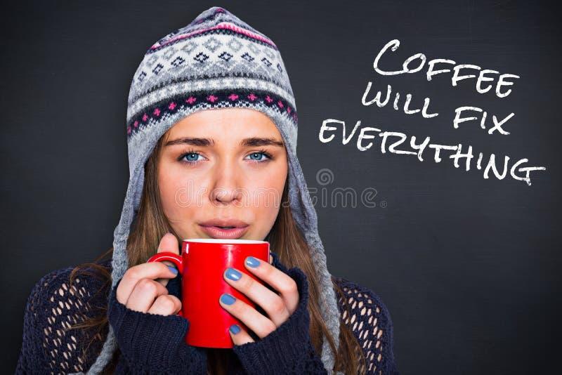 Imagem composta da mulher bonita no café bebendo da roupa morna fotografia de stock
