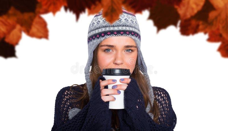Imagem composta da mulher bonita no café bebendo da roupa morna foto de stock