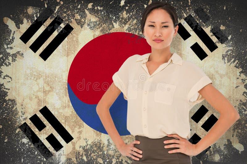 Imagem composta da mulher de negócios asiática com mãos nos quadris fotografia de stock