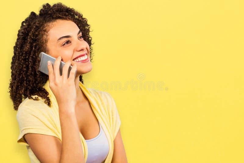 Imagem composta da mulher de negócios de sorriso que usa o telefone esperto ao olhar afastado imagens de stock royalty free