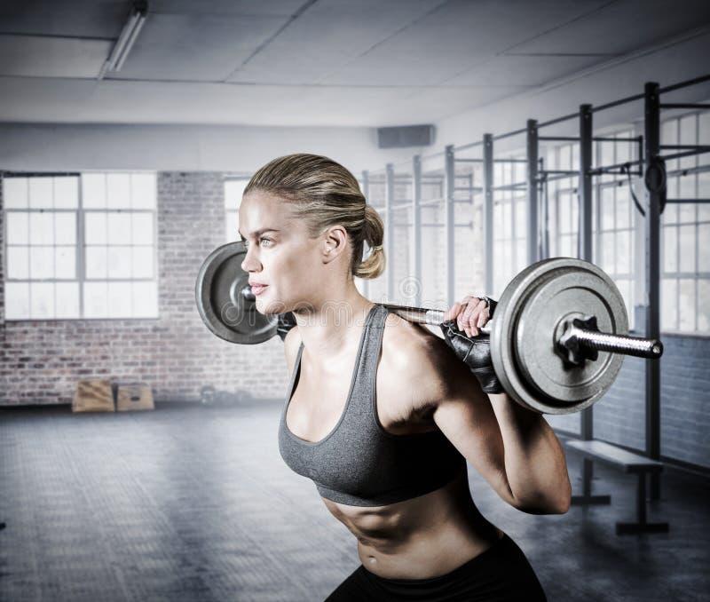 Imagem composta da mulher muscular que levanta o barbell pesado fotos de stock royalty free