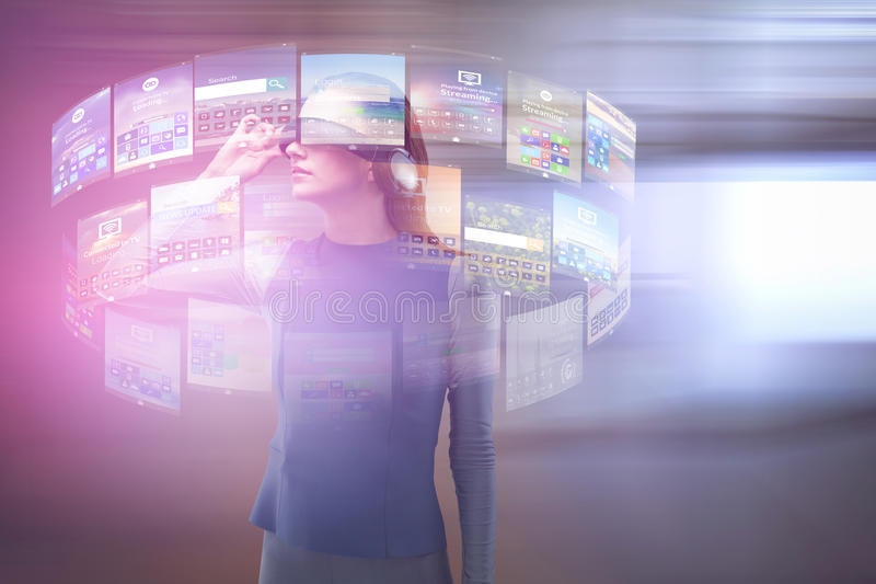 Imagem composta da mulher que experimenta auriculares da realidade virtual fotografia de stock
