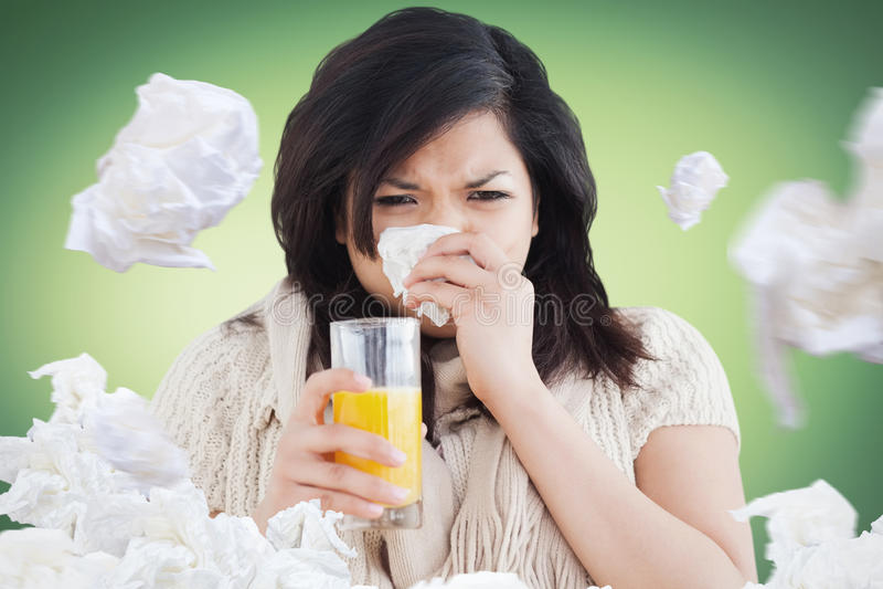 Imagem composta da mulher que guarda um vidro do suco de laranja ao espirrar foto de stock