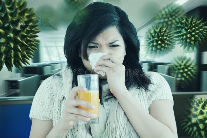 Imagem composta da mulher que guarda um vidro do suco de laranja ao espirrar fotos de stock