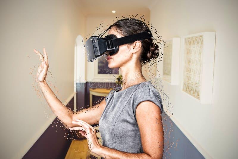 Imagem composta da opinião lateral a jovem mulher que gesticula ao usar vidros video virtuais foto de stock