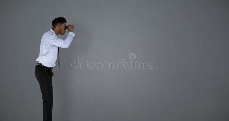 Imagem composta da opinião lateral o homem de negócios que olha através dos binóculos imagens de stock