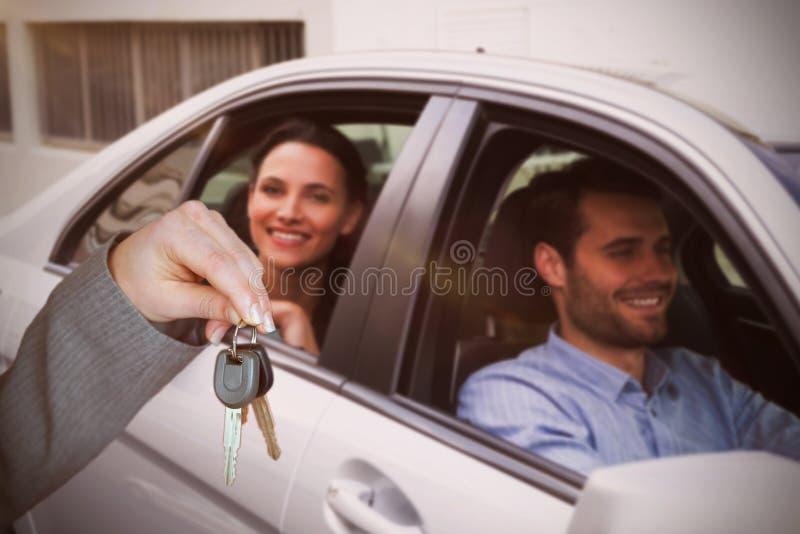 Imagem composta da pessoa que entrega chaves a alguma outra pessoa foto de stock royalty free