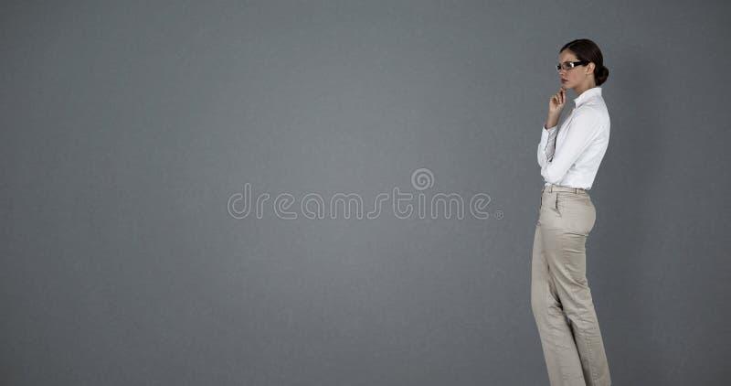 Imagem composta da posição pensativa da mulher de negócios fotografia de stock