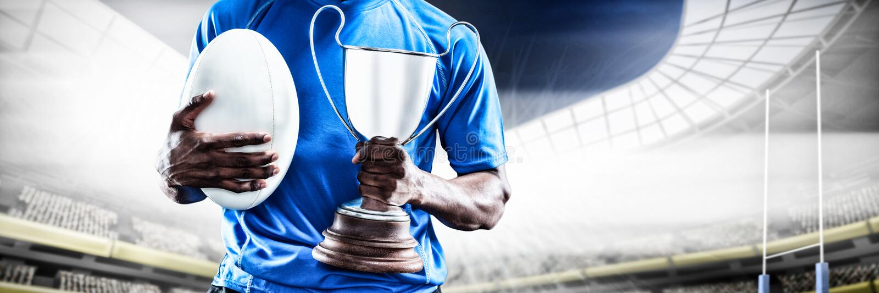 Imagem composta da seção meados de do desportista que guarda o troféu e a bola de rugby imagens de stock