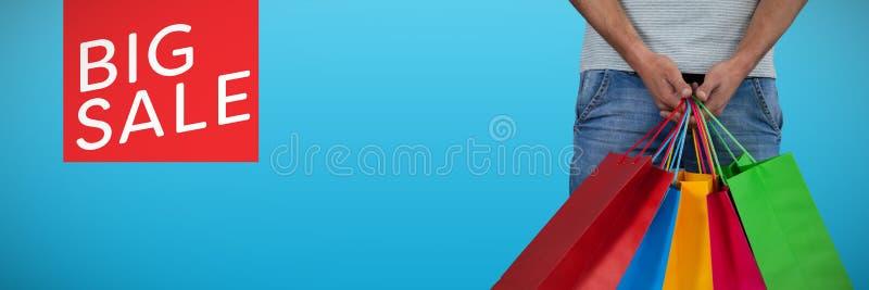 Imagem composta da seção mestra do homem que leva o saco de compras colorido contra o fundo branco imagens de stock