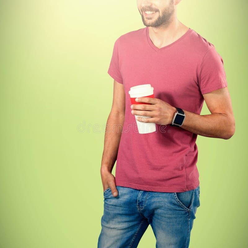 Imagem composta da seção mestra do modelo de sorriso que guarda o copo de café descartável foto de stock