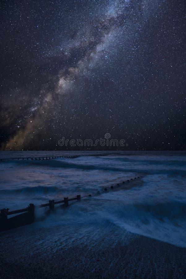 Imagem composta da Via Látea vibrante sobre a paisagem das ondas que deixam de funcionar na praia imagens de stock royalty free