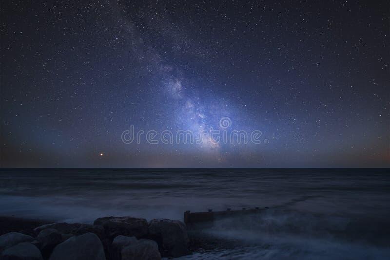 Imagem composta da Via Látea vibrante sobre a paisagem do cais no mar imagens de stock
