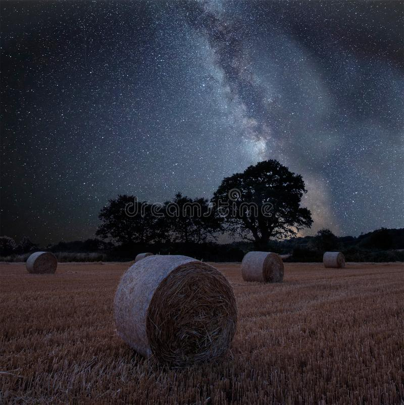 Imagem composta da Via Látea vibrante sobre a paisagem do campo do feno fotografia de stock