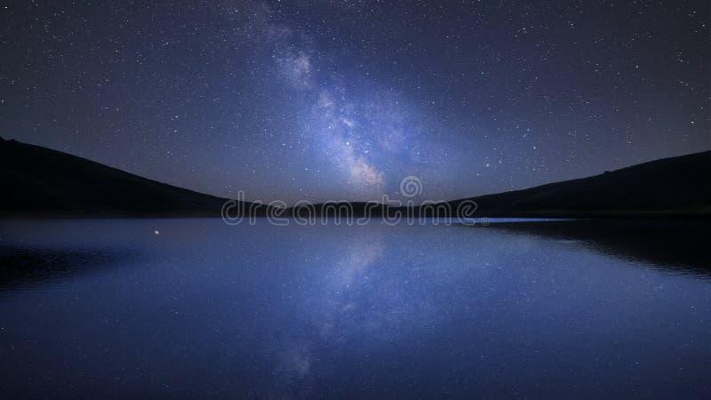 Imagem composta da Via Látea vibrante sobre a paisagem do lago calmo com reflexões foto de stock