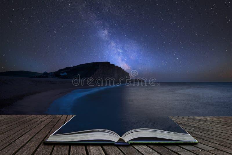 Imagem composta da Via Látea vibrante sobre a paisagem da exposição longa da baía ocidental em Dorset que sai de páginas no livro imagens de stock