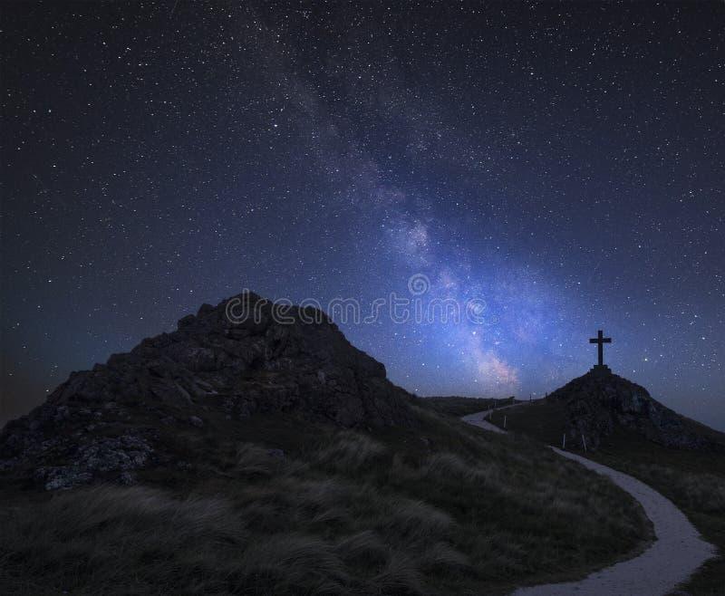 Imagem composta da Via Látea vibrante sobre a paisagem da ilha de Ynys Llanddwyn com o farol do Mawr de Twr no fundo fotografia de stock royalty free