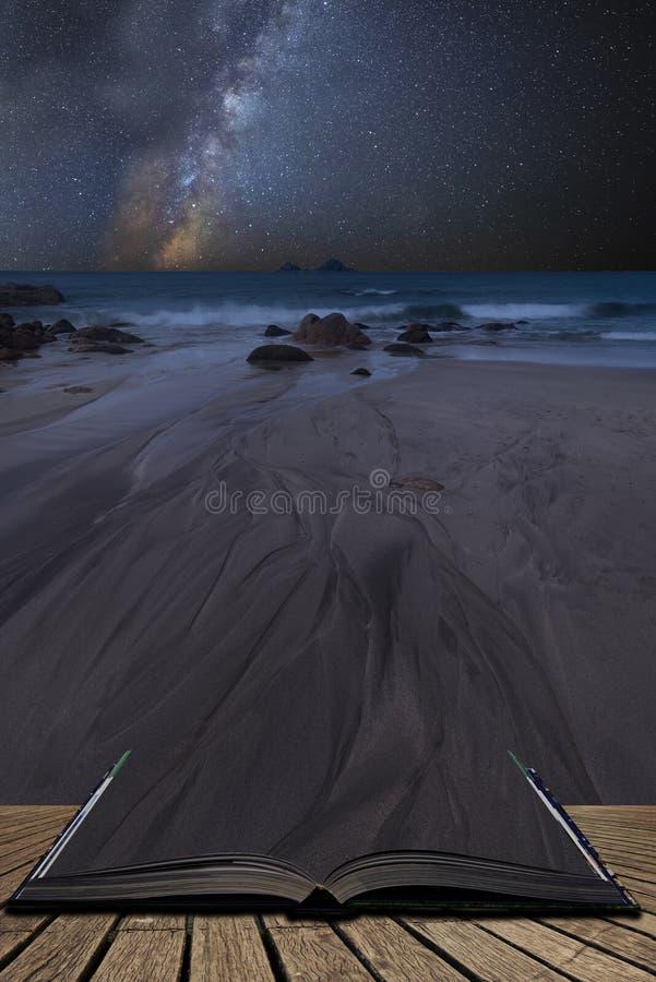 Imagem composta da Via Látea vibrante sobre a paisagem da praia bonita que sai de páginas no livro mágico da história foto de stock