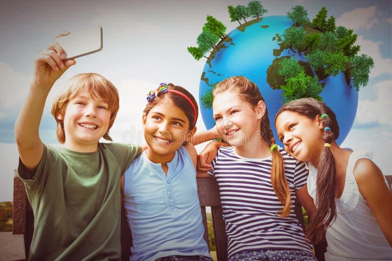 Imagem composta das crianças felizes que tomam o selfie no parque fotografia de stock royalty free