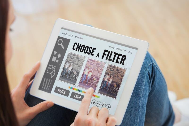 Imagem composta de adolescente usando um PC da tabuleta que senta-se no assoalho fotografia de stock royalty free