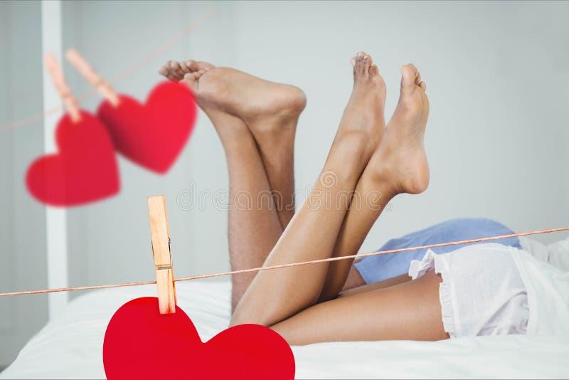 Imagem composta de corações vermelhos e dos pares de suspensão que encontram-se na cama com pé cruzado fotografia de stock