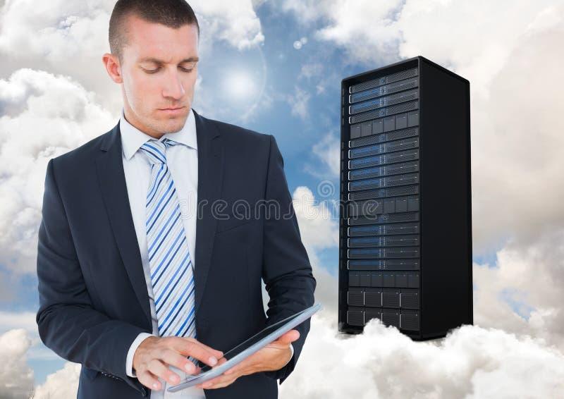 Imagem composta de Digitas do homem de negócios que usa a tabuleta digital contra a torre do servidor imagem de stock