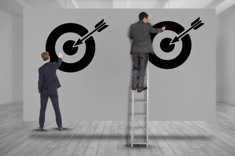 Imagem composta de Digitas dos executivos que ajustam alvos na parede imagem de stock royalty free