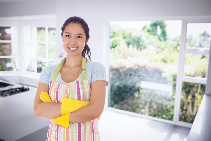 Imagem composta de luvas e do avental de borracha vestindo de sorriso da mulher foto de stock