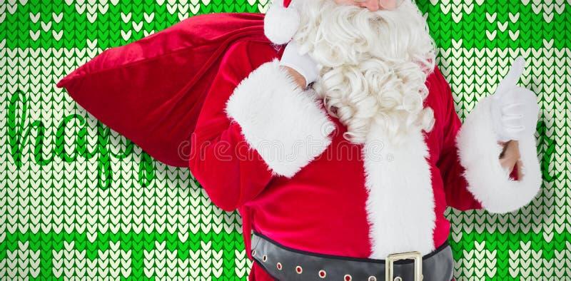 Imagem composta de Papai Noel com seus saco e polegares acima fotografia de stock