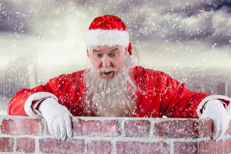 Imagem composta de Papai Noel que espreita sobre a parede fotografia de stock