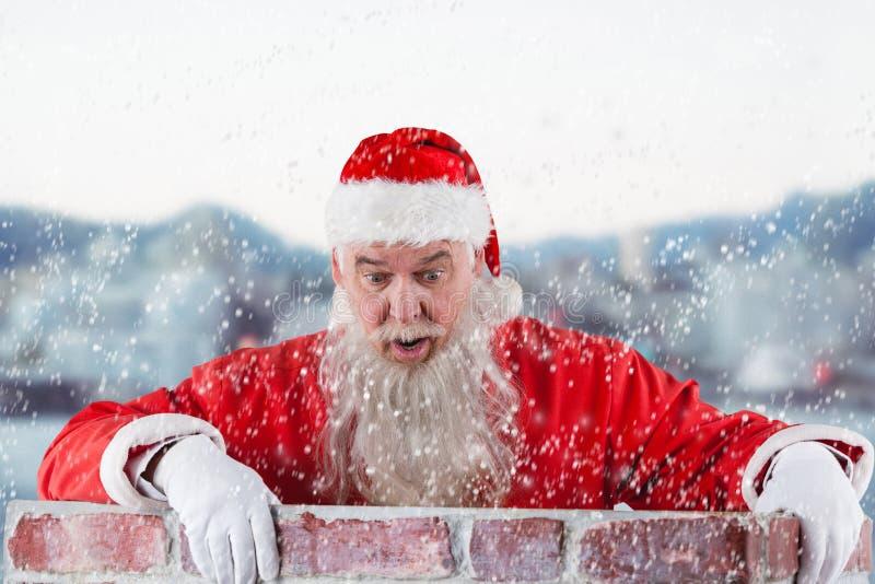 Imagem composta de Papai Noel que espreita sobre a parede imagens de stock