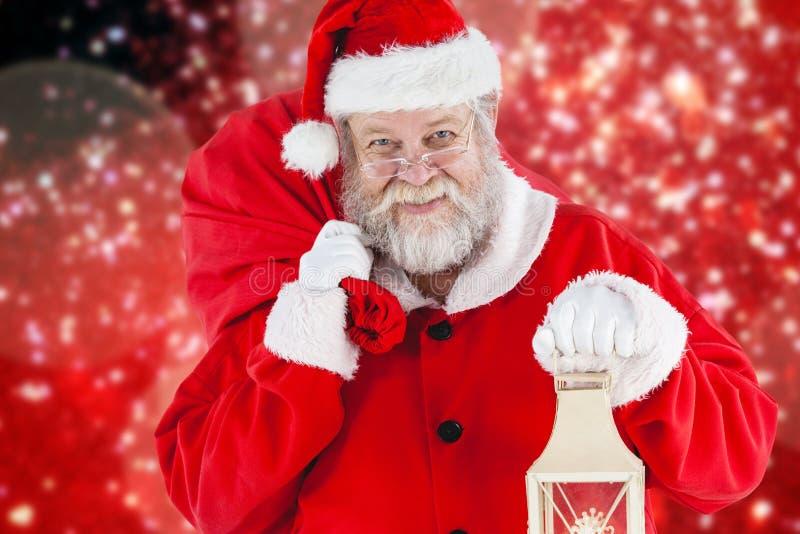 Imagem composta de Papai Noel que guarda o saco e a lanterna do Natal imagem de stock royalty free