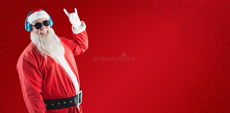Imagem composta de Papai Noel que mostra o sinal do yo da mão ao escutar a música em fones de ouvido imagem de stock royalty free