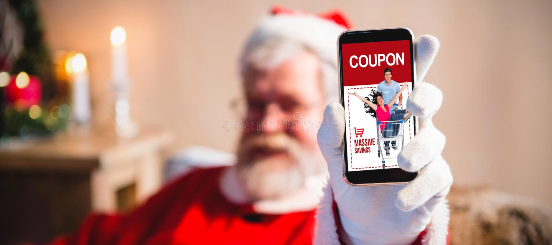 Imagem composta de Papai Noel que senta e que mostra seu smartphone imagem de stock