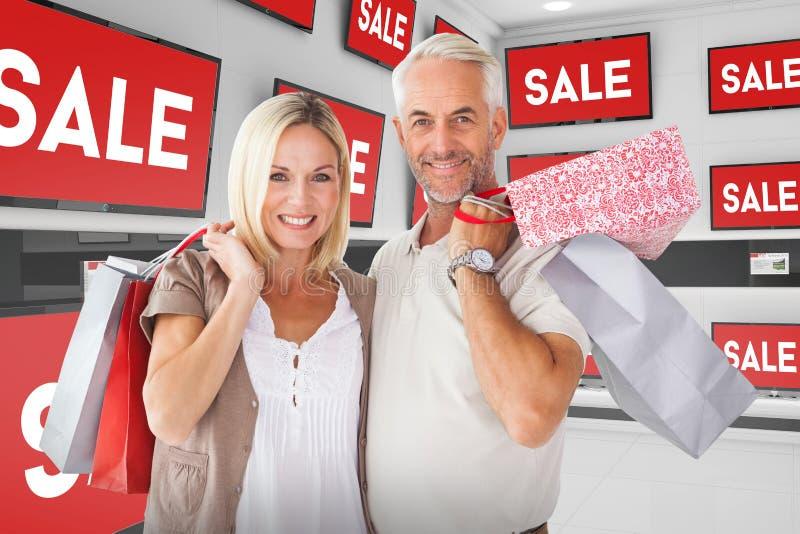 Imagem composta de pares felizes com sacos de compras fotos de stock