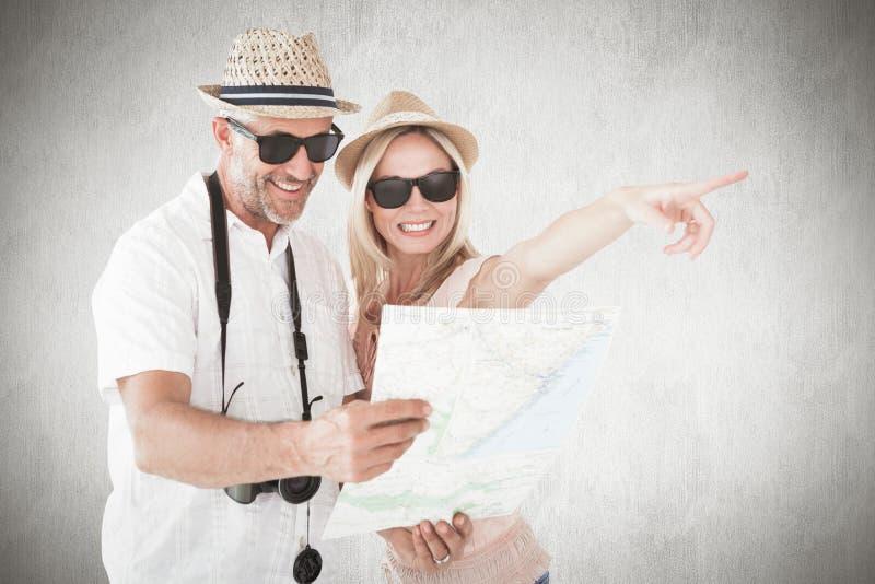 Imagem composta de pares felizes do turista usando o mapa e apontar imagens de stock royalty free