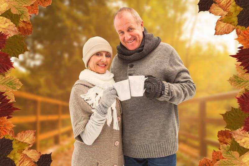 A imagem composta de pares maduros felizes no inverno veste guardar canecas fotografia de stock