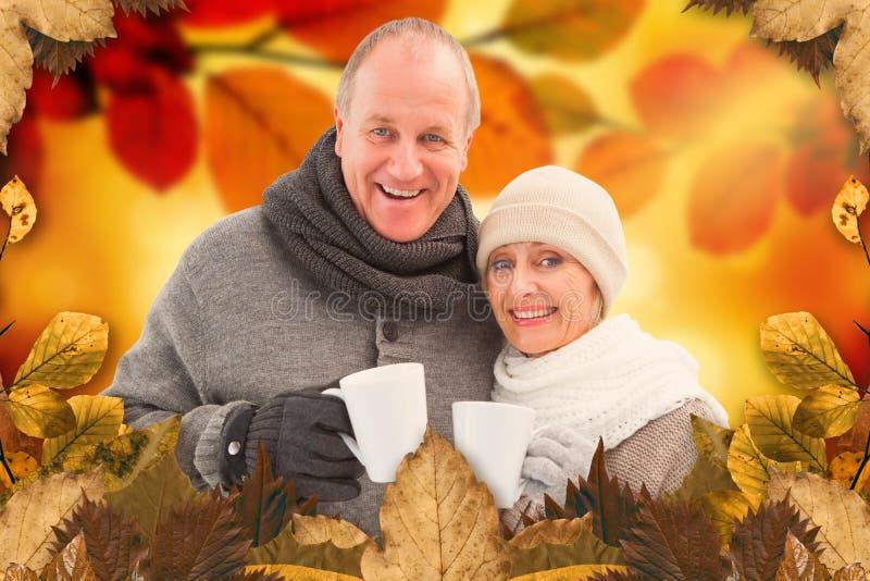 A imagem composta de pares maduros felizes no inverno veste guardar canecas imagens de stock