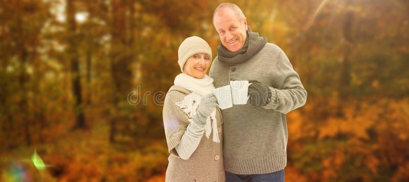 A imagem composta de pares maduros felizes no inverno veste guardar canecas foto de stock