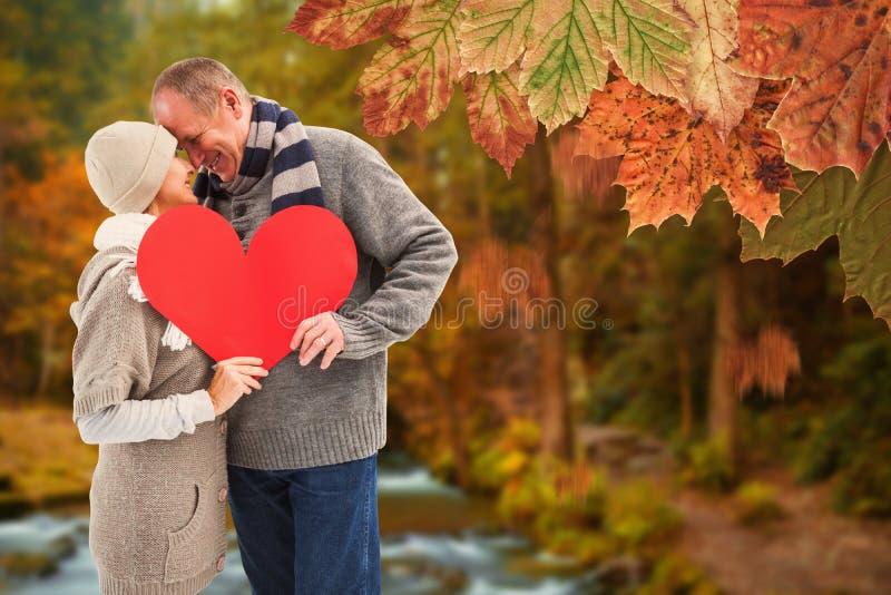 A imagem composta de pares maduros felizes no inverno veste guardar o coração vermelho imagens de stock