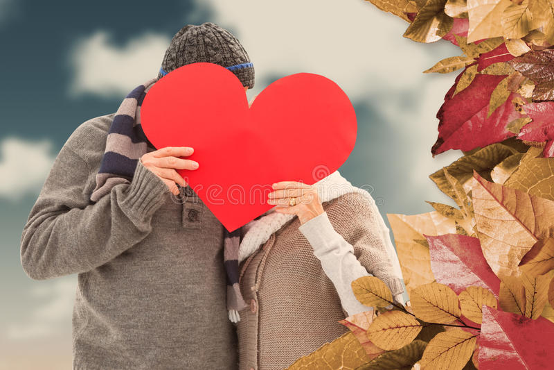 A imagem composta de pares maduros felizes no inverno veste guardar o coração vermelho fotografia de stock royalty free