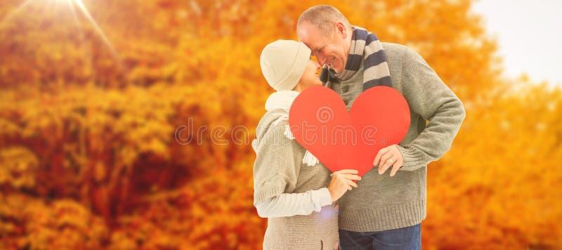 A imagem composta de pares maduros felizes no inverno veste guardar o coração vermelho imagens de stock royalty free