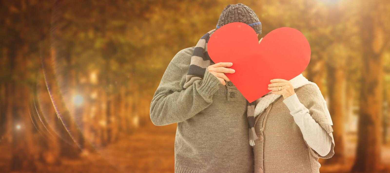 A imagem composta de pares maduros felizes no inverno veste guardar o coração vermelho fotos de stock
