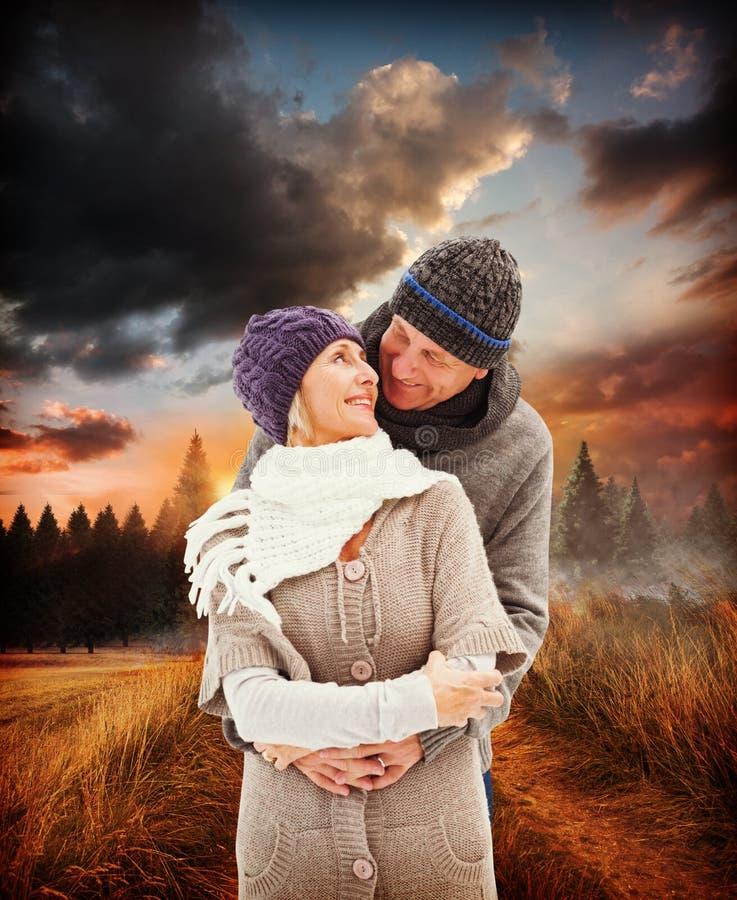 A imagem composta de pares maduros felizes no inverno veste o abraço imagem de stock royalty free