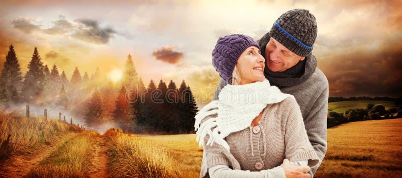 A imagem composta de pares maduros felizes no inverno veste o abraço fotografia de stock